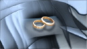 Royalty Free Video of Rotating Wedding Rings on a Grey Pillow