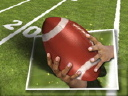 Royalty Free Video of Hands on a Football in Front of a Football Field
