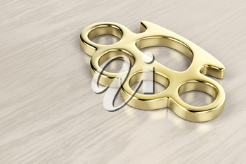 Golden brass knuckles on wooden background