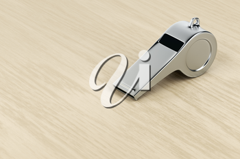Silver referee whistle on wood desk