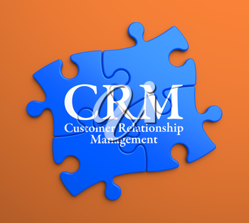CRM - Customer Relationship Management - Written on Blue Puzzle Pieces on Orange Background. Business Concept.