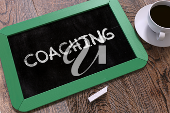 Coaching Concept Hand Drawn on Green Chalkboard on Wooden Table. Business Background. Top View. 3D Render.