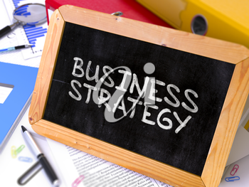 Business Strategy Handwritten on a Chalkboard. Composition with Small Chalkboard on Background of Working Table with Office Folders, Stationery, Reports. Blurred Background. Toned Image. 3D Render.