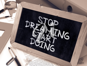 Stop Dreaming, Start Doing - Chalkboard with Hand Drawn Text, Stack of Office Folders, Stationery, Reports on Blurred Background. Toned Image. 3D Render.