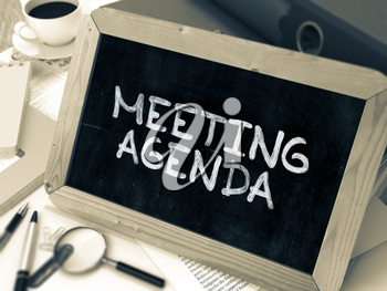 Meeting Agenda Concept Hand Drawn on Chalkboard on Working Table Background. Blurred Background. Toned Image. 3D Render.