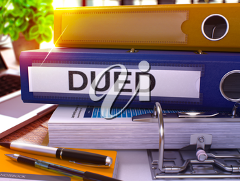 DUED - Due Diligence - Blue Ring Binder on Office Desktop with Office Supplies and Modern Laptop. DUED Business Concept on Blurred Background. DUED - Toned Illustration. 3D Render.