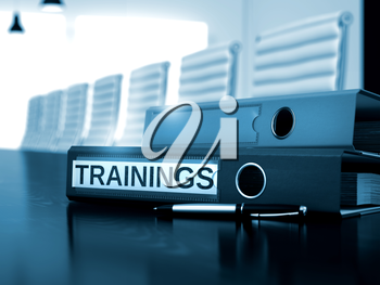 Folder with Inscription Trainings on Working Desk. Trainings - Illustration. Trainings - Business Concept on Toned Background. 3D Render.