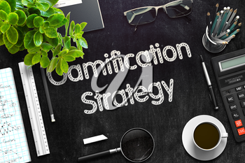 Gamification Strategy. Business Concept Handwritten on Black Chalkboard. Top View Composition with Chalkboard and Office Supplies. 3d Rendering. Toned Illustration.