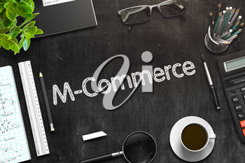 M-Commerce Handwritten on Black Chalkboard. Top View of Black Office Desk with a Lot of Business and Office Supplies on It. 3d Rendering. Toned Image.