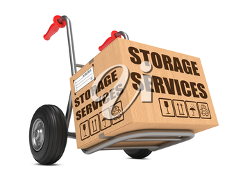 Cardboard Box with Storage Services Slogan on Hand Truck White Background.