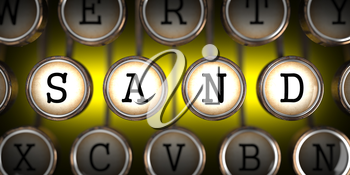 Sand - Word on Old Typewriter's Keys on Yellow Background.