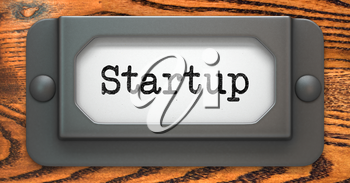 Startup - Inscription on File Drawer Label on a Wooden Background.