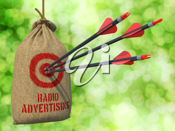 Radio Advertising - Three Arrows Hit in Red Target on a Hanging Sack on Natural Bokeh Background.
