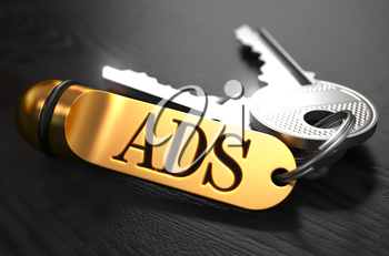 Keys and Golden Keyring with the Word Ads over Black Wooden Table with Blur Effect.