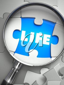 Life - Word on the Place of Missing Puzzle Piece through Magnifier. Selective Focus.