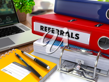 Red Ring Binder with Inscription Referrals on Background of Working Table with Office Supplies, Laptop, Reports. Toned Illustration. Business Concept on Blurred Background.