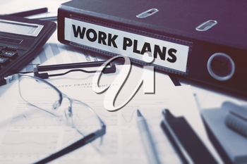 Work Plans - Office Folder on Background of Working Table with Stationery, Glasses, Reports. Business Concept on Blurred Background. Toned Image.