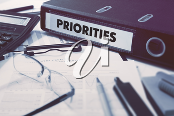 Priorities - Office Folder on Background of Working Table with Stationery, Glasses, Reports. Business Concept on Blurred Background. Toned Image.