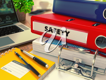 Red Office Folder with Inscription Safety on Office Desktop with Office Supplies and Modern Laptop. Business Concept on Blurred Background. Toned Image.
