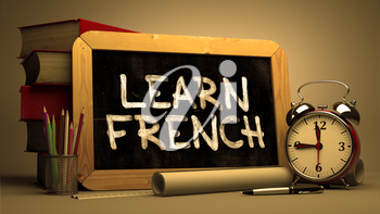 Learn French - Motivational Quote Handwritten on Chalkboard. Time Concept. Composition with Chalkboard and Stack of Books, Alarm Clock and Scrolls on Blurred Background. Toned Image.