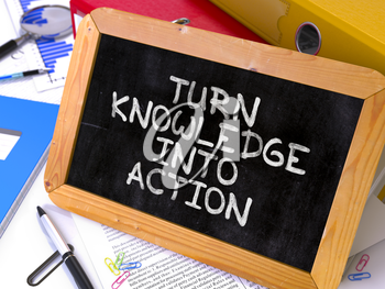 Motivational Quote. Turn Knowledge into Action - Hand Drawn on Chalkboard on Working Table Background. Blurred Background. Toned Image.