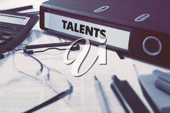 Talents - Office Folder on Background of Working Table with Stationery, Glasses, Reports. Business Concept on Blurred Background. Toned Image.