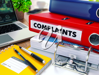 Complaints - Red Ring Binder on Office Desktop with Office Supplies and Modern Laptop. Business Concept on Blurred Background. Toned Illustration.