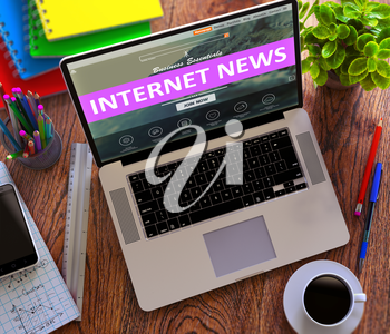 Internet News Concept. Modern Laptop and Different Office Supply on Wooden Desktop background.