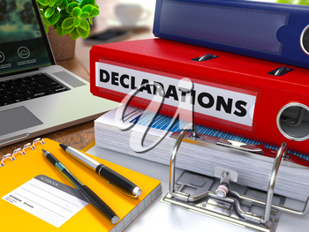 Red Ring Binder with Inscription Declarations on Background of Working Table with Office Supplies, Laptop, Reports. Toned Illustration. Business Concept on Blurred Background.