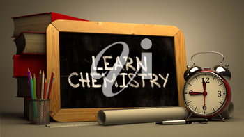 Learn Chemistry Handwritten on Chalkboard. Motivational Quote. Composition with Chalkboard and Stack of Books, Alarm Clock and Scrolls on Blurred, Toned Image.
