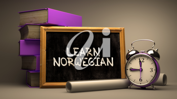 Motivational Quote. Learn Norwegian - Chalkboard with Hand Drawn Text, Stack of Books, Alarm Clock and Rolls of Paper on Blurred Background. Toned Image.