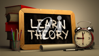 Learn Theory Handwritten by white Chalk on a Blackboard. Composition with Small Chalkboard and Stack of Books, Alarm Clock and Rolls of Paper on Blurred Background. Toned Image.