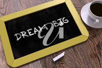 Dream Big - Yellow Chalkboard with Hand Drawn Text and White Cup of Coffee on Wooden Table.  Inspirational Quote. Top View.
