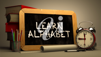 Learn Alphabet.  Inspirational Quote Handwritten on Chalkboard. Time Concept. Composition with Chalkboard and Stack of Books, Alarm Clock and Scrolls on Blurred Background. Toned Image.