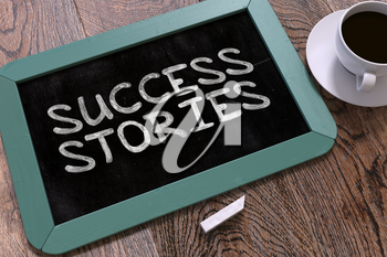 Success Stories Handwritten on Blue Chalkboard. Business Concept. Composition with Chalkboard and Cup of Coffee. Top View Image.