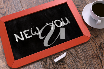 New You - Red Chalkboard with Hand Drawn Text and White Cup of Coffee on Wooden Table. Top View.