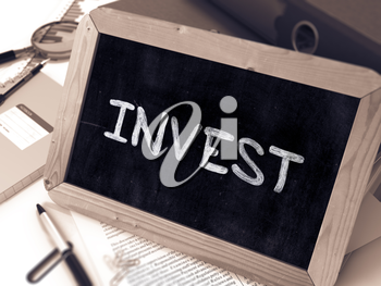 Invest Handwritten by White Chalk on a Blackboard. Composition with Small Chalkboard on Background of Working Table with Office Folders, Stationery, Reports. Blurred Background. Toned Image.