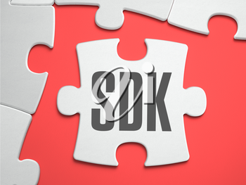 SDK -  Software Development Kit - Text on Puzzle on the Place of Missing Pieces. Scarlett Background. Close-up. 3d Illustration.