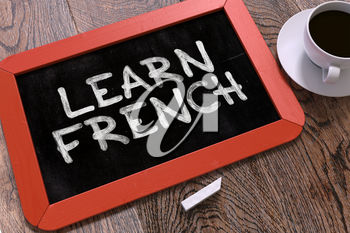 Learn French Concept Hand Drawn on Red Chalkboard on Wooden Table. Business Background. Top View. 3d Render.