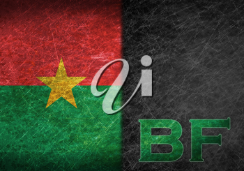 Old rusty metal sign with a flag and country abbreviation - Burkina Faso