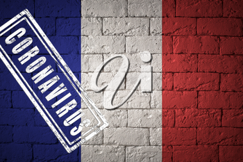 Flag of the France with original proportions. stamped of Coronavirus. brick wall texture. Corona virus concept. On the verge of a COVID-19 or 2019-nCoV Pandemic.