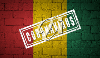 Flag of the Guinea on brick wall texture. stamped of Coronavirus. Corona virus concept. On the verge of a COVID-19 or 2019-nCoV Pandemic. Novel Chinese Coronavirus outbreak