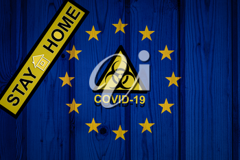 flag of European Union in original proportions. Quarantine and isolation - Stay at home. flag with biohazard symbol and inscription COVID-19.