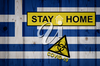 Flag of the Greece in original proportions. Quarantine and isolation - Stay at home. flag with biohazard symbol and inscription COVID-19.