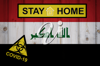 Flag of the Iraq in original proportions. Quarantine and isolation - Stay at home. flag with biohazard symbol and inscription COVID-19.