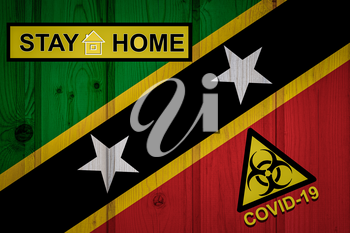 Flag of the Saint Kitts and Nevis in original proportions. Quarantine and isolation - Stay at home. flag with biohazard symbol and inscription COVID-19.
