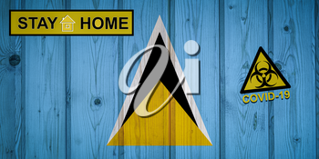 Flag of the Saint Lucia in original proportions. Quarantine and isolation - Stay at home. flag with biohazard symbol and inscription COVID-19.
