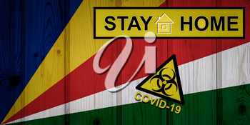 Flag of the Seychelles in original proportions. Quarantine and isolation - Stay at home. flag with biohazard symbol and inscription COVID-19.